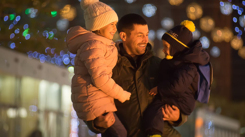 A parent with two children in front of festive lights