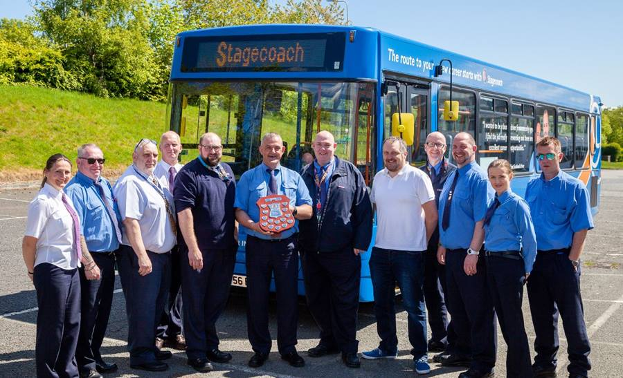 East Scotland bus drivers stand in front of a training bus with award winner Steven Fiddes and Managing Director Douglas Robertson